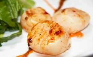 Grilled scallops with lettuce, indian style, closeup shot