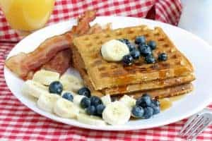 Homemade waffles with syrup, bananas, blueberries and a side of bacon.