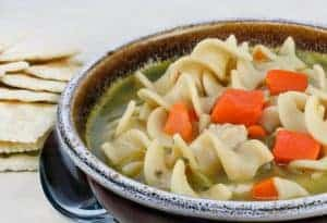 A crock of hearty chicken noodle soup, close-up.  Crackers to the side.