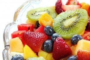 Fresh fruit salad in a crystal bowl.  Luscious healthy eating, with kiwi fruit, strawberries, blueberries, canteloupe, watermelon, mango, oranges, and passionfruit